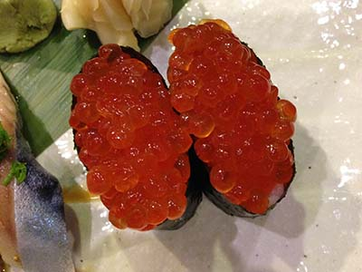 A sushi roll of nori wrapped into a cylinder and filled with salmon roe (ikura).