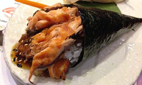 A cone of nori wrapped around grilled salmon skin.