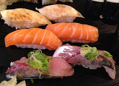 Three groups of nigiri sushi with white, red and silver colors of fish.
