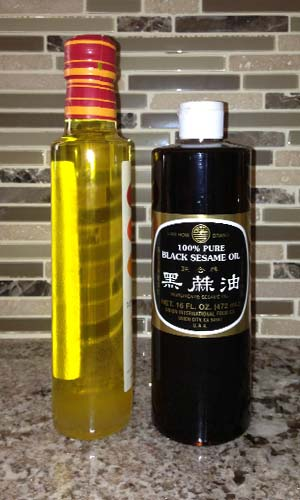 Bottles of cold pressed white and black sesame oils showing light and very dark colors.