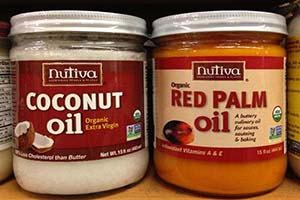 Jars of palm and coconut oil showing the red and white colors respectively.